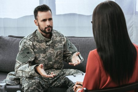 sad soldier with ptsd talking at psychiatrist and gesturing while sitting on couch during therapy session
