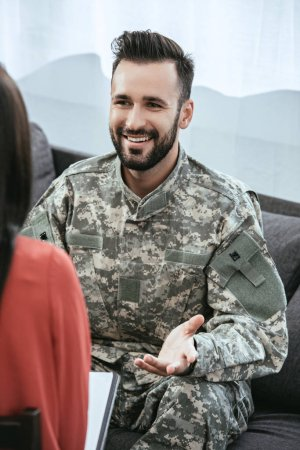 smiling soldier talking at psychiatrist and gesturing while sitting on couch during therapy session