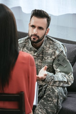 Photo for Depressed soldier talking at psychiatrist and gesturing while sitting on couch during therapy session - Royalty Free Image