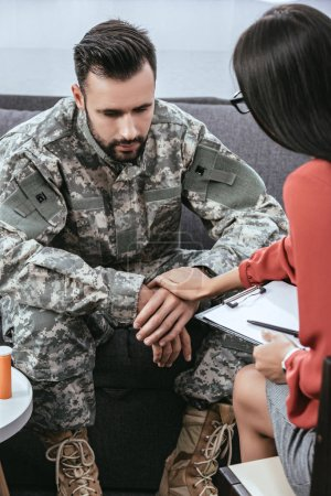female psychiatrist supporting depressed soldier with post traumatic syndrome during therapy session