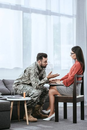 mad soldier talking at psychiatrist and gesturing during therapy session