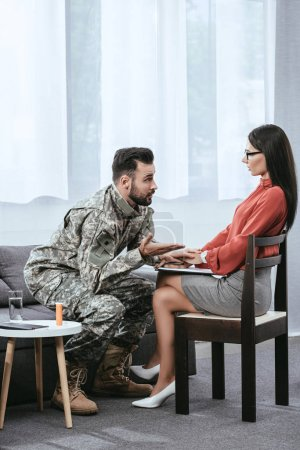 angry soldier talking at psychiatrist and gesturing during therapy session