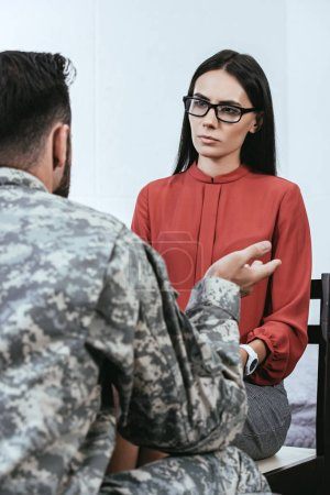 rear view of soldier talking at psychiatrist and gesturing during therapy session