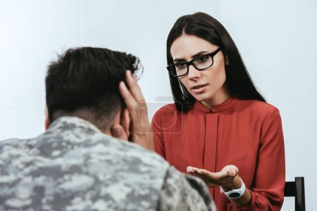 Photo for Female psychiatrist talking to depressed soldier with ptsd during therapy session - Royalty Free Image