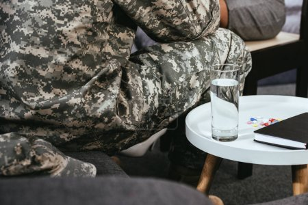 Photo for Cropped shot of soldier sitting on couch with glass of water and pills on table - Royalty Free Image