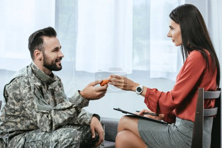 Photo for Psychiatrist giving container of pills to smiling soldier during therapy session - Royalty Free Image