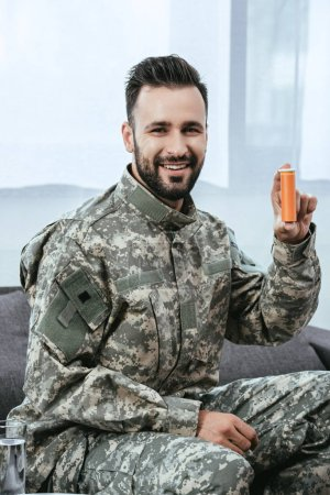 Photo for Happy young soldier holding plastic jar of pills and looking at camera - Royalty Free Image
