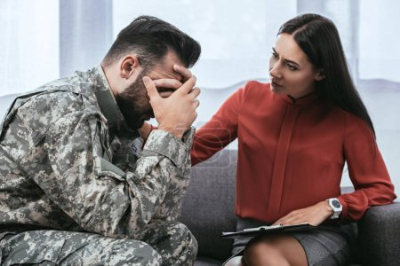 Photo for Soldier and psychiatrist sitting on couch during therapy session - Royalty Free Image