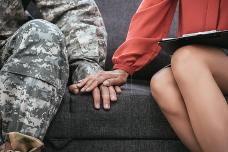 Photo for Cropped shot of soldier and psychiatrist holding hands during therapy session - Royalty Free Image