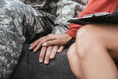 Photo for Cropped shot of soldier and female psychiatrist holding hands during therapy session - Royalty Free Image