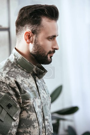 Photo for Side view of army man in military uniform at home - Royalty Free Image