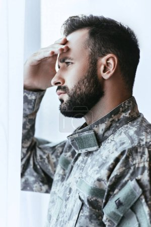 Photo for Depressed army man in military uniform with post-traumatic stress disorder touching his head and looking away - Royalty Free Image