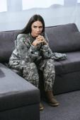 soldado mujer pensativa en uniforme militar con TEPT sentado en sofá y mirando lejos