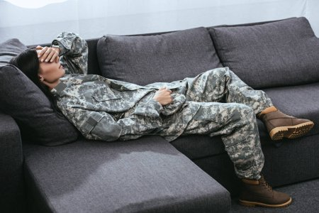 Photo for Female soldier in military uniform with ptsd lying on couch - Royalty Free Image