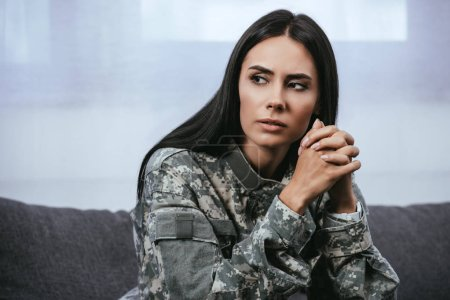 Photo for Close-up portrait of thoughtful female soldier in military uniform with ptsd sitting on couch and looking away - Royalty Free Image