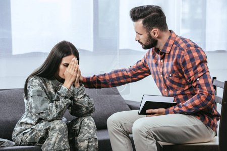 psychiatrist supporting female soldier during therapy session