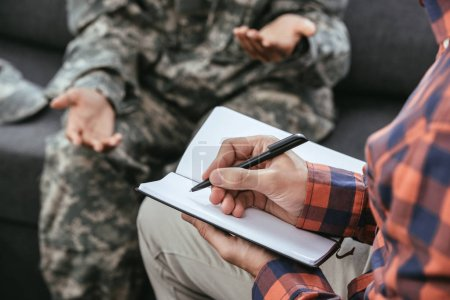 cropped shot psychiatrist writing notes during therapy session with female soldier