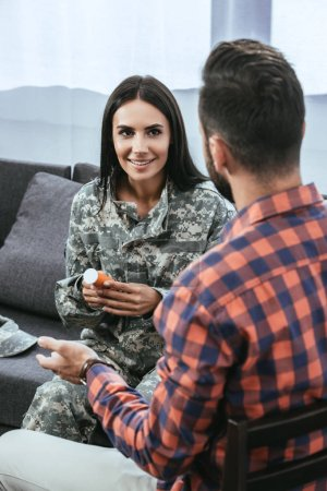 psychiatrist giving container of pills to female soldier during therapy