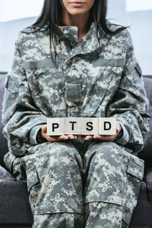Photo for Cropped shot of young female soldier in military uniform sitting on couch and holding wooden cubes with PTSD sign - Royalty Free Image
