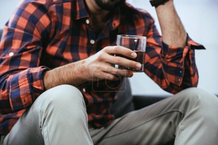 cropped shot of young man holding glass of whiskey while sitting on couch