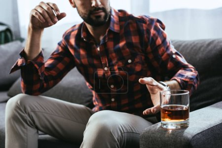 cropped shot of young man taking glass of whiskey while sitting on couch
