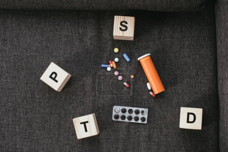 Photo for Top view of wooden cubes with posttraumatic stress disorder abbreviation signs (PTSD) lying on couch with various pills - Royalty Free Image