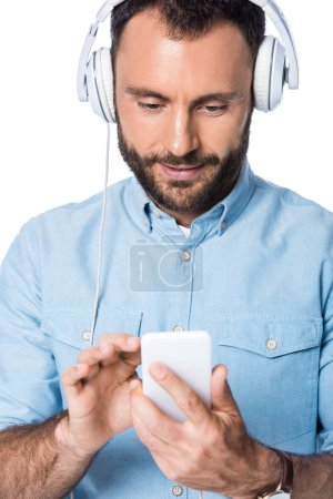 smiling man listening music with headphones and using smartphone isolated on white
