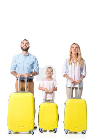 family with yellow travel bags looking up isolated on white