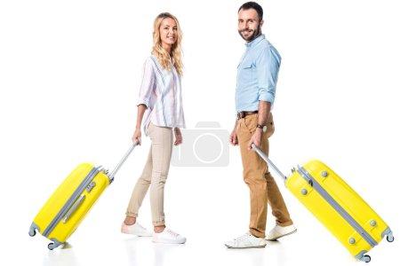 glückliches Paar mit gelben Reisetaschen auf weißem Grund