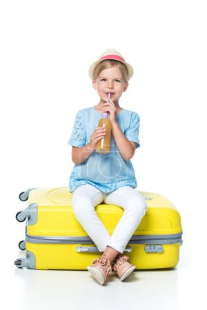 child with drink sitting on yellow baggage isolated on white