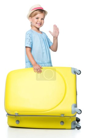 happy child waving and standing with yellow travel bag isolated on white
