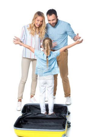 surprised parents with daughter standing in travel bag isolated on white