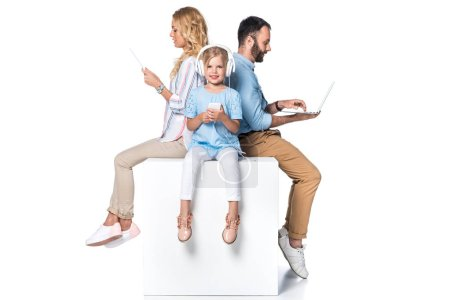 family using digital devices and sitting on white cube isolated on white