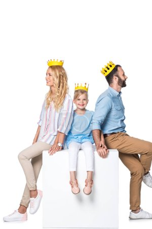 family with yellow cardboard crowns sitting on white cube isolated on white