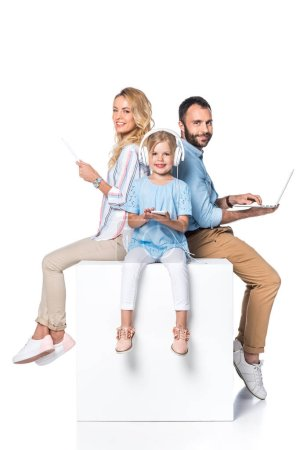 family using digital gadgets and sitting on white cube isolated on white