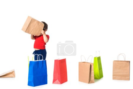 Photo pour Enfant jouer avec des sacs à provisions isolés sur blanc  . - image libre de droit