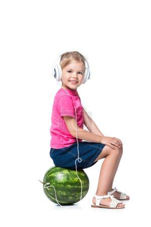 Foto de Sonriente niño escucha música con auriculares aislados en blanco, el concepto de tecnología - Imagen libre de derechos