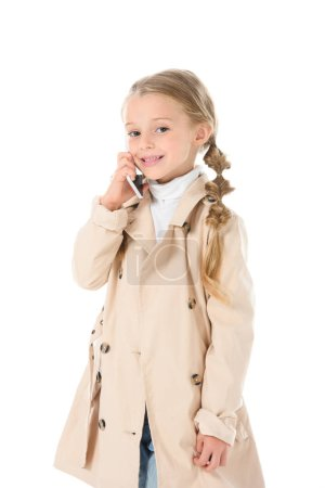 adorable child in autumn beige coat talking on smartphone, isolated on white
