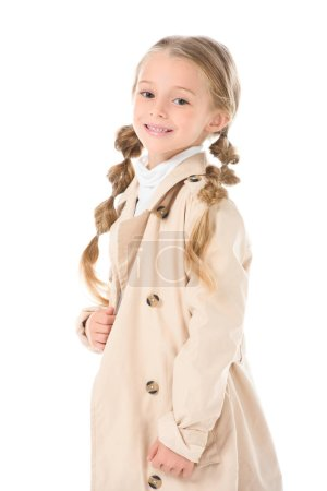 smiling child posing in beige coat, isolated on white