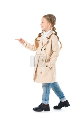 Photo for Adorable kid in beige coat pointing somewhere, isolated on white - Royalty Free Image