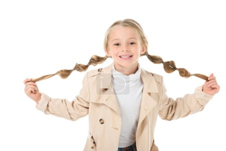 happy child with braids posing in beige coat, isolated on white