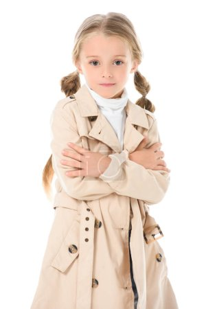 stylish kid posing in beige coat with crossed arms, isolated on white