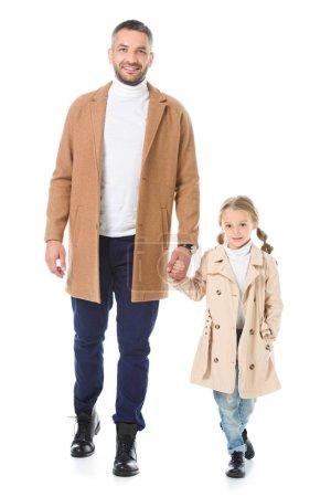 Photo pour Père et fille en manteaux beige tenant la main et marchant isolés sur blanc - image libre de droit