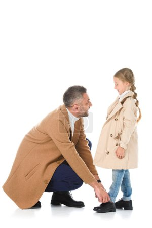 father and daughter in beige coats looking at each other, isolated on white