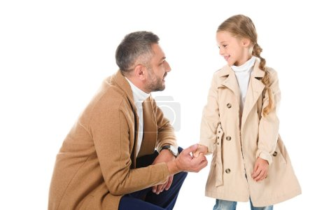 father and daughter in beige coats holding hands and looking at each other, isolated on white
