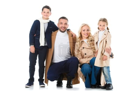 stylish family hugging with kids in beige coats, isolated on white