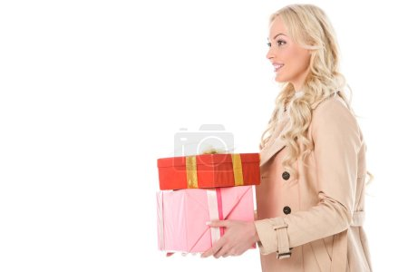 smiling blonde woman in beige coat holding gifts, isolated on white