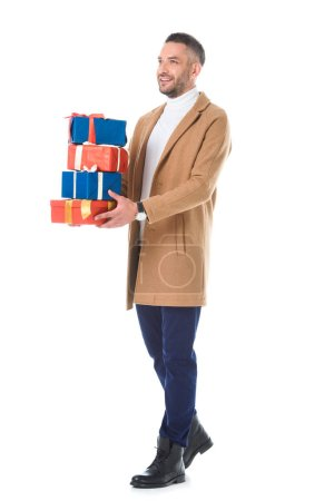 handsome man in trendy beige coat holding presents, isolated on white