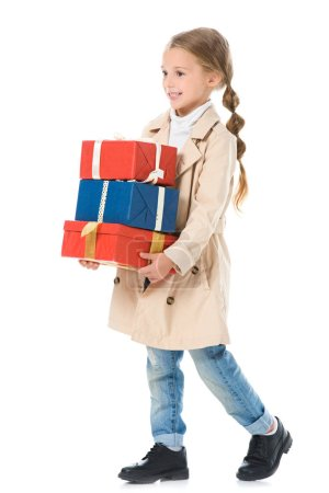 Photo for Adorable happy kid in beige coat holding presents, isolated on white - Royalty Free Image