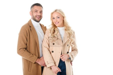 Photo for Beautiful smiling couple posing in beige coats, isolated on white - Royalty Free Image